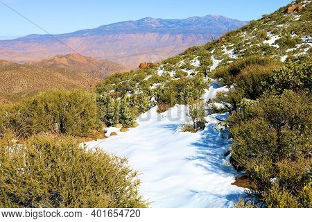 Arid Mountain Slope Covered With Chaparral Plants Besides Snow Overlooking The High Desert Plateau T