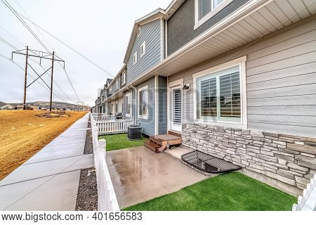 Townhouses Exterior View With Grassy Backyards Enclosed In Low Picket Fences
