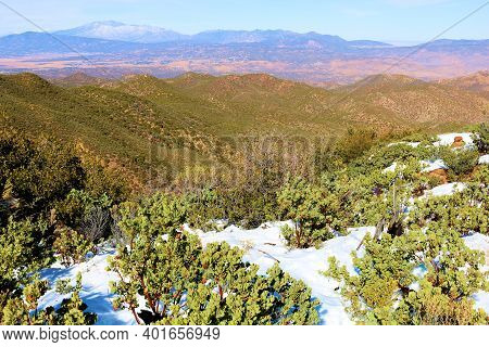 Windswept Mountain Ridge Covered With Chaparral Shrubs Surrounded By Snow Overlooking The High Deser