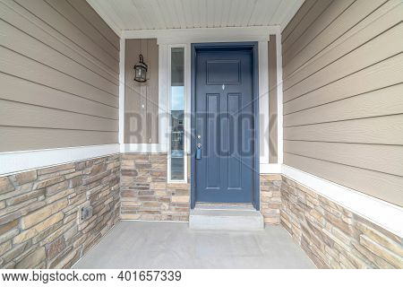 Blue Front Door Of A Home With Sidelight And Outdoor Wall Lamp At The Entrance