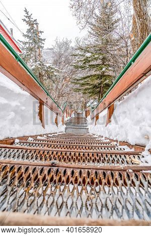 Outdoor Mountain Stairway With Metal Treads And Handrails Against Snow And Trees