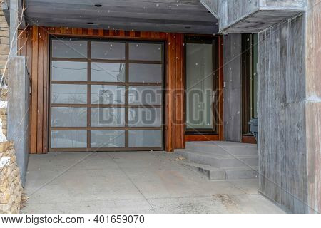 Glass Front Door And Glass Paned Garage Door Of Home Against Wood And Brick Wall
