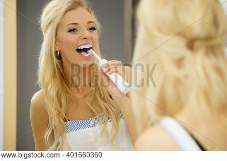 Beautiful Blonde Woman Brushing Her Teeth Using Electric Toothbrush Having Fun. Hygiene, Body Care C