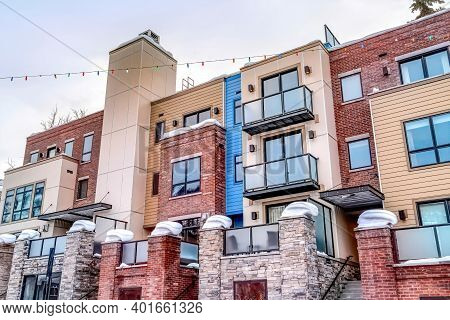 Facade Of Modern Townhouses With Snowy Flat Roof And Stairs At Front Entrances