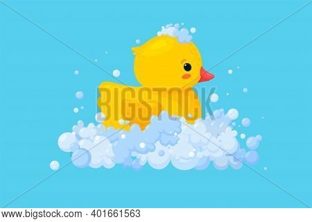 Rubber Duck In Soap Foam With Bubbles Isolated In Blue Background. Side View Of Yellow Plastic Duckl