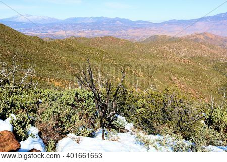 Barren Mountain Ridge With Chaparral Plants Surrounded By Snow Overlooking Arid Badlands Taken On Th