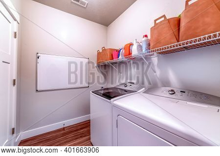Laundry Room With Washing Machine And Dryer Under Detergents And Soaps On Rack