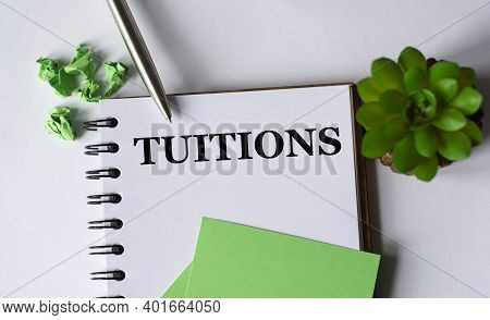 Tuitions - Word In A Notebook With A Pen, A Green Paper And A Cactus On A White Background.