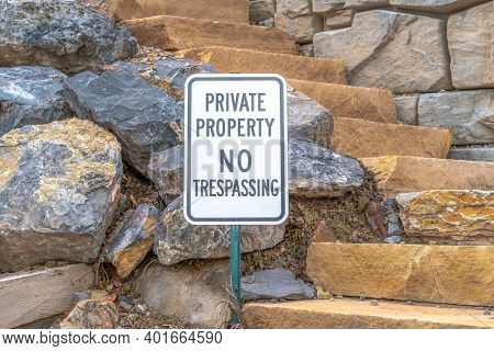 Private Property No Trespassing Sign Against Jagged Rocks And Stone Stairway