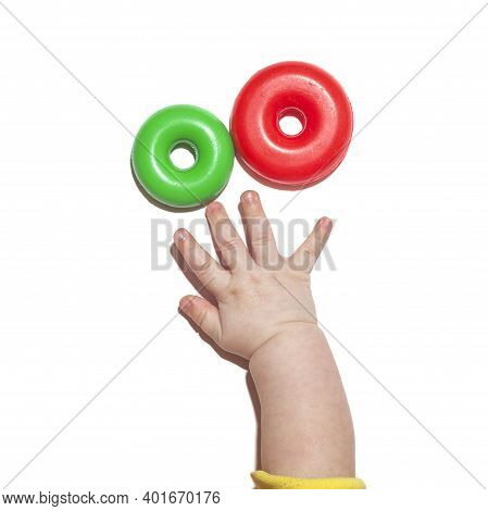 Child's Hand Reaches For Toys. Baby Palm Isolated On White Background