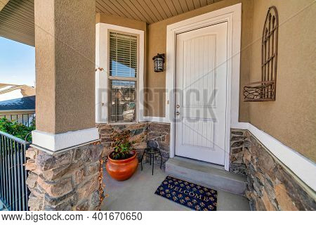 Front Porch Of Home With Single Hung Window And White Front Door At The Entrance