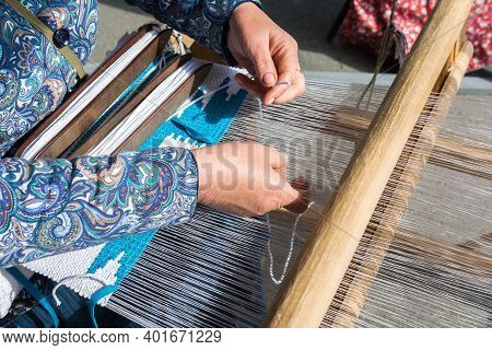 Folk Art Festival. A woman makes fabric on a hand loom. The fabric is made by hand.