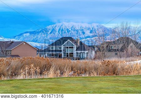 Residences In The Snowy Valley Against Majestic Frosted Mountain And Cloudy Sky