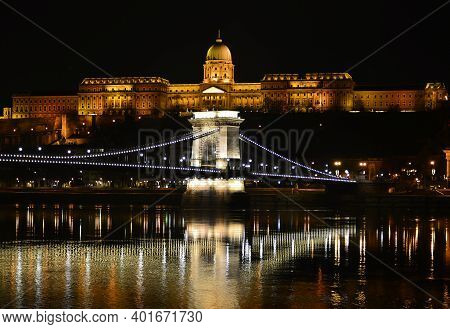 Night Budapest, Chain Bridge On The Background Of Buda Castle, Reflection Of Night Lights On The Wat