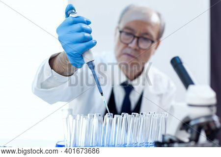 Chemist Scientist Working With Dropper Pipette And Blue Substance In Modern Laboratory. Senior Profe