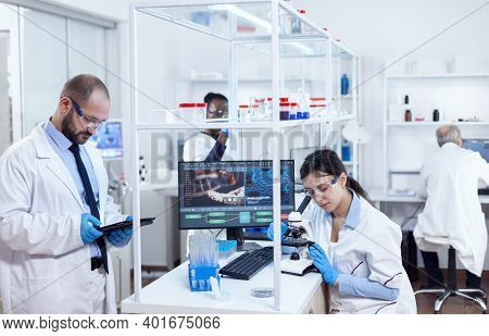 Mix Raced Scientist Using Tablet Pc And Microscope In Lab. Team Of Researchers Doing Pharmacology En