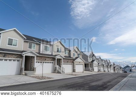 Townhouses On A Scenic Subrban Landscape Against Lake Mountain And Cloudy Sky
