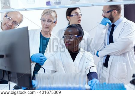Team Of Scientists With Multiethnicity Discussing Chemical Formula In Front Of Computer. Black Healt