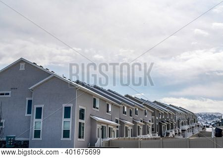 Side View Of Townhouses With Snowy Gable Roofs Against Overcast Sky In Winter