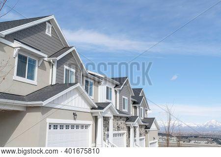 Facade Of Townhouses On A Suburban Neighborhood Community Against Sky View