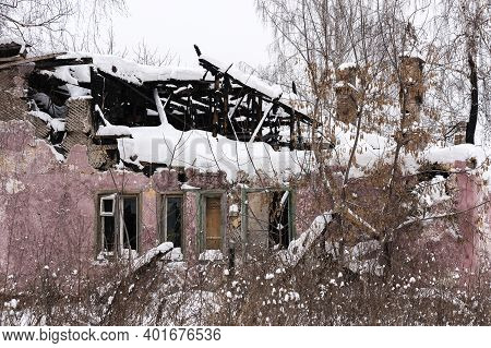 The Burnt Ruins Of An Old Residential Building Covered With Snow