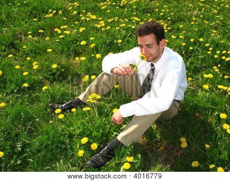 Man Smelling A Dandelion