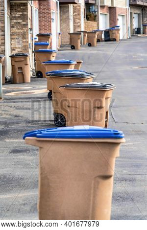 Grabage Bins With Wheels In Front Of Townhouses Along A Paved Neighborhood Road