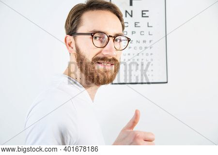 Man Looking At The Camera After Reading An Eye Test Chart. An Ophthalmologist, An Optometrist Eye Ex