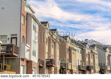 Townhouses On Scenic Neighborhood In Winter With Snowy Mountain Peak Background