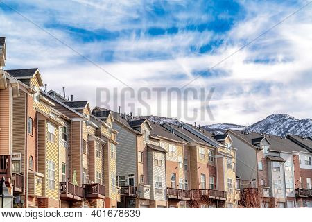 Wasatch Mountain Snowy Peak Behind Row Of Townhouses Under Blue Sky And Clouds