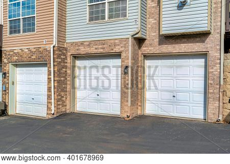 Townhouses With White Garage Doors Against Brick Exterior Wall And Wood Siding
