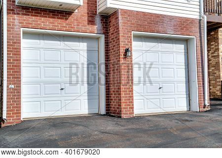 White Panelled Garage Doors Of Townhouses In The Neighborhood On A Sunny Day