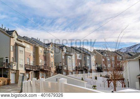 Scenic Neighborhood In Winter With Townhouses Overlooking Snowy Mountain Peak