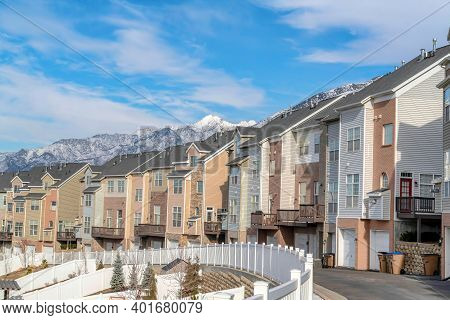 Townhouses On A Winter Residential Landscape With Snowy Mountain Peak Background