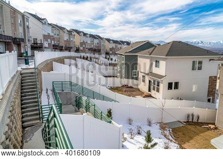 Snowy Neighborhood Landscape With Stairs And Road Amid Homes And Townhouses