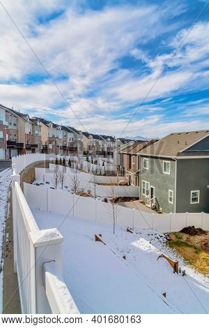 Homes With Fenced Backyards Along Road And Townhouses On A Winter Landscape