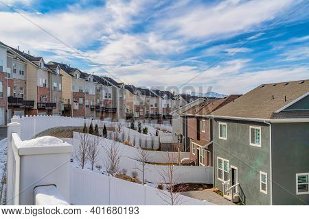 Townhouses With Balconies And Homes With Fenced Yards Against Cloudy Blue Sky