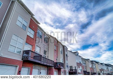 Facade Of Townhouses Against Scenic Skyscape Of Vibrant Blue Sky And Clouds
