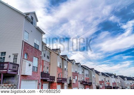 Row Of Three Storey Townhouses In The Valley Under Vibrant Blue Sky With Clouds
