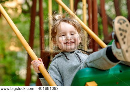 Cute Baby Girl On A Seesaw Swing At The Playground.cute Baby Girl On A Swing Seesaw. On The Playgrou