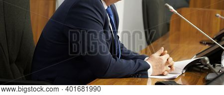 A Man Sits At A Table With Monitors And Speakerphones And Speaks Into A Microphone. Negotiation, Dis