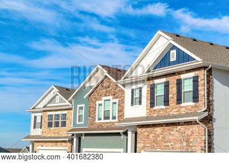 Exterior View Of Homes With Gable Roofs Stone Brick And Wooden Siding Walls