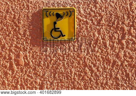 Invalid On Wheelchair And Ring Bell Sign On The Wall. Disabled People Help