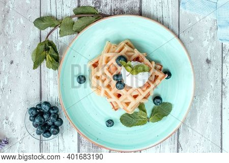 Fresh Baked Homemade Classic Belgian Waffles Topped With Icecream, Fresh Blueberries And Mint On Woo
