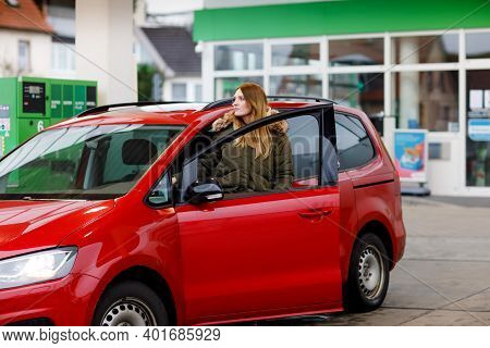 Young Attractive Woman Gets Out Of Her Car By Gas Station To Refill Car With Petrol Or Gas. People R