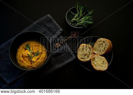 Bowl With Yam And Carrots With Leeks Puree Soup And Rosemary On A Black  Smooth Surface. White Bread