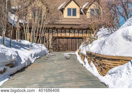 Driveway That Leads To Garage Door Of Home Nestled Amid Sunny Snowy Neighborhood