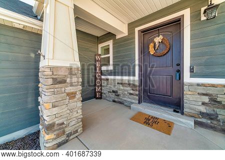 Open Porch At Home Facade With Stone Wall Wood Siding And Wreath On Front Door