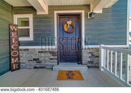 Home With Open Porch And Entrance Decorated With Wreath And Welcome Sign Board