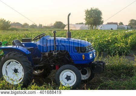 A Farm Tractor Without A Driver Stands On A Farm Field At Sunset. Subsidizing And Supporting Farms,